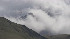 Paraglider flying high in the clouds Stock Footage
