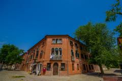 MURANO, ITALY - JUNE 16, 2015: Orange house in the corner of Murano street Stock Photos