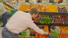 man choosing a chilli peppers at supermarket - stock footage