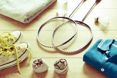 Rackets for badminton, shuttlecock, polo shirts, shoes, towel and water. Stock Photos