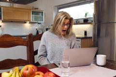Shocked middle-aged woman with laptop Stock Photos