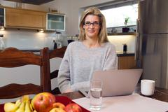Middle-aged attractive woman using a laptop computer at home - stock photo