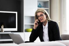 Middle-aged woman working from home - stock photo