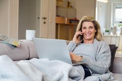 Blonde woman working from living room - stock photo