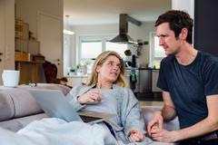 Couple at home on sofa looking at laptop - stock photo
