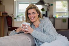 Attractive blonde woman drinking coffe at home - stock photo