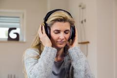 Pretty blonde woman listening to music on couch at home - stock photo