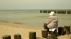 Granny sitting on a beam at the beach Stock Footage