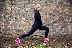 Woman stretching her body in front of ancient wall in park - stock photo
