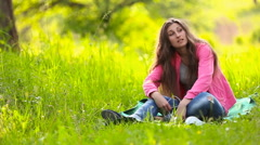 Girl sits in nature and that it says indignantly. Stock Footage
