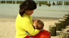 Mother breastfeeds baby, sitting near sea Stock Footage
