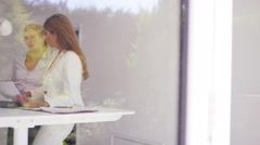 4K Businesswomen working in modern office, view from outside looking in Stock Footage