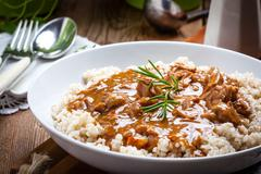 Cooked barley porridge and stew of pork. - stock photo