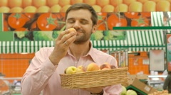 Smiling man in supermarket holding wicker basket with apricots - stock footage