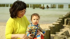 Mother with baby sitting on a stumps near sea Stock Footage