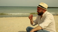 Man stretch and yawn, sitting at the beach - stock footage