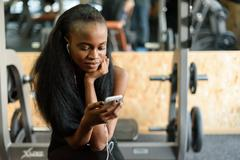 Portrait of charming black young woman with luxury long hair texting on her Stock Photos