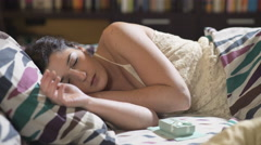 Pretty woman awakness: she finds a gift and a letter in her bed Stock Footage
