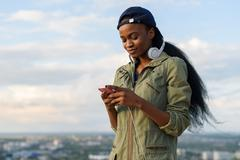Charming african american girl listen to music and relaxing. Smiling young black Stock Photos