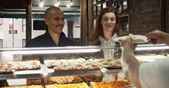 Couple receiving pizza from take away counter Stock Footage
