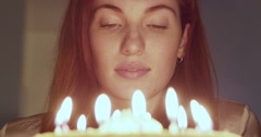 Woman blowing out candle on her birthday cake - stock footage
