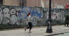 Young woman listening to music while jogging on the city street Stock Footage