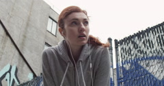 Young woman feeling exhausted after jogging in the city - stock footage