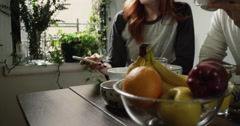 Couple looking at the mobile phone and talking while having breakfast at home - stock footage