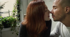 Couple kissing while having breakfast at home - stock footage