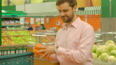 Man choosing carrots in grocery store - stock footage