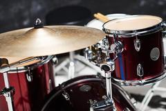 Modern drum set on black background in room - stock photo