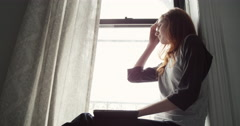 Beautiful woman sitting on windowsill with laptop - stock footage