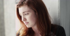 Depressed young woman crying near the window - stock footage