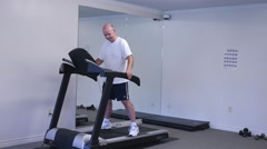 Senior Man Walking On A Treadmill Wearing Work Out Clothes Stock Footage