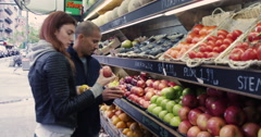 Young couple purchasing a fresh fruits in market - stock footage
