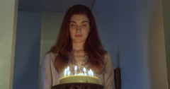 Beautiful woman holding a birthday cake with burning candles - stock footage
