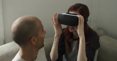 Smiling young couple using VR headset at home Stock Footage