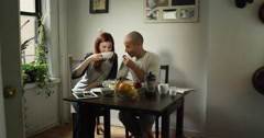 Young couple talking while having breakfast at home - stock footage