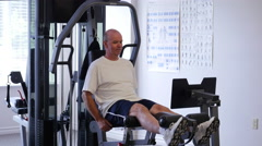 Baby Boomer Man Doing Leg Curls In A Gym On A Multi Gym Machine Stock Footage