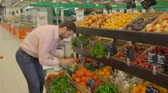 Man selecting fresh cucumbers in grocery store department. - stock footage