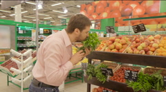 Man selecting fresh herbs in grocery store department. - stock footage