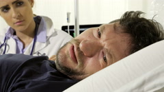 Dolly shot of sick sad man in hospital crying looked by female doctor Stock Footage