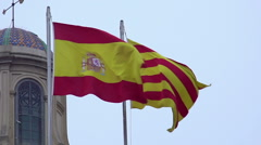 Spanish and Catalan flags with coat of arms fluttering in wind against blue sky Stock Footage