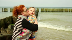 Granny kisses a baby at the beach Stock Footage