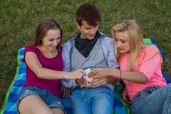 Now my turn! Three friends  fighting for a mobile phone. - stock photo