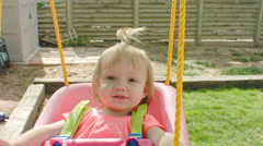 Little Girl swinging in baby swing Stock Footage