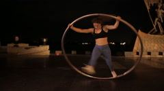 Woman on cyr wheel doing acrobatic trick - stock footage