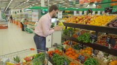 Man selecting fresh peppermint in grocery store department. Stock Footage
