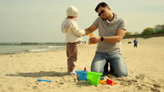 Father spends time with daughter and talking on a cell phone at the beach Stock Footage