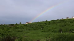 Summer rainbow above hill houses Stock Footage
